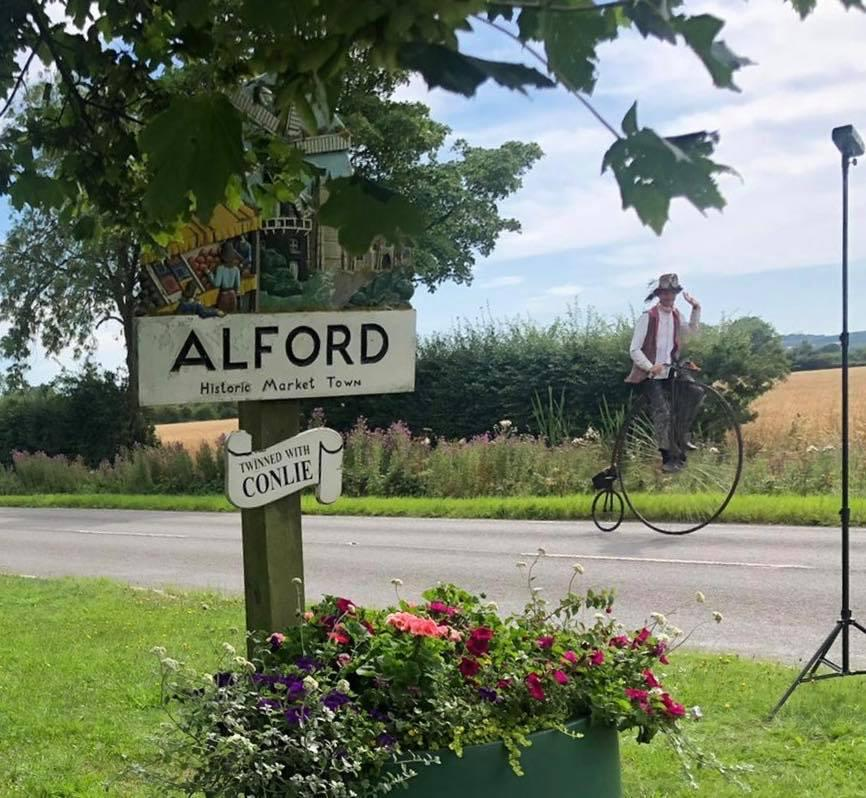 Photo of Alford Town Sign with man on Penny Farthing